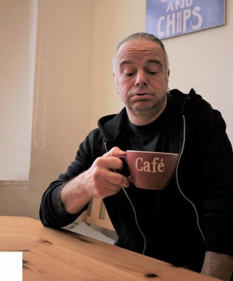 Herr W. sitzt am Tisch und schaut ein wenig skeptisch in eine Tasse.
