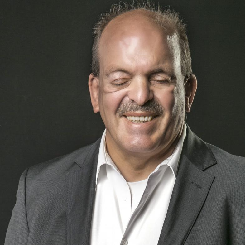 Portraitfoto von Dr. Michael Richter mit grauem Jacket, weißem Hemd und einem Lächeln mit eher geschlossenen Augen.