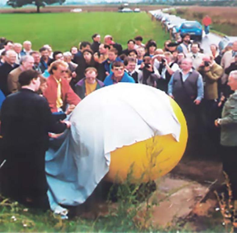 Zur Einweihung des Planetenlehrpfades 1995 wird vor einer Zuschauermengen ein weißes Tuch von der Sonne gezogen.