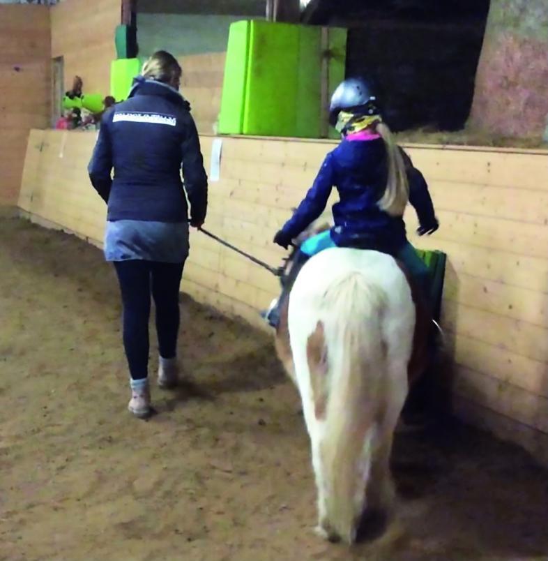 Ein Mädchen beim Reiten auf einem Pony in der Reithalle