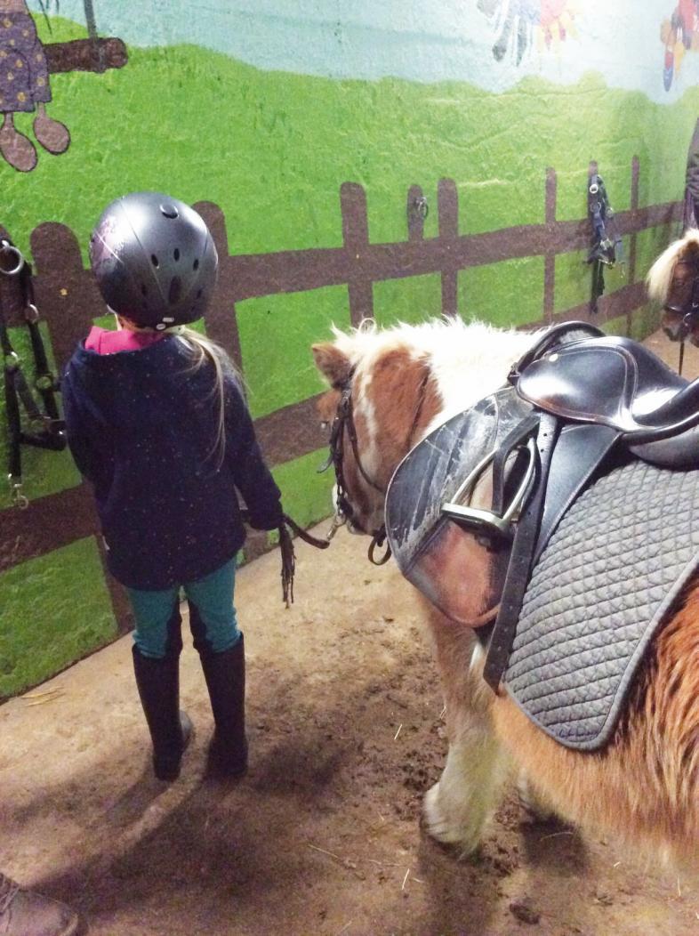 Ein Mädchen führt ein Pony am Zügel