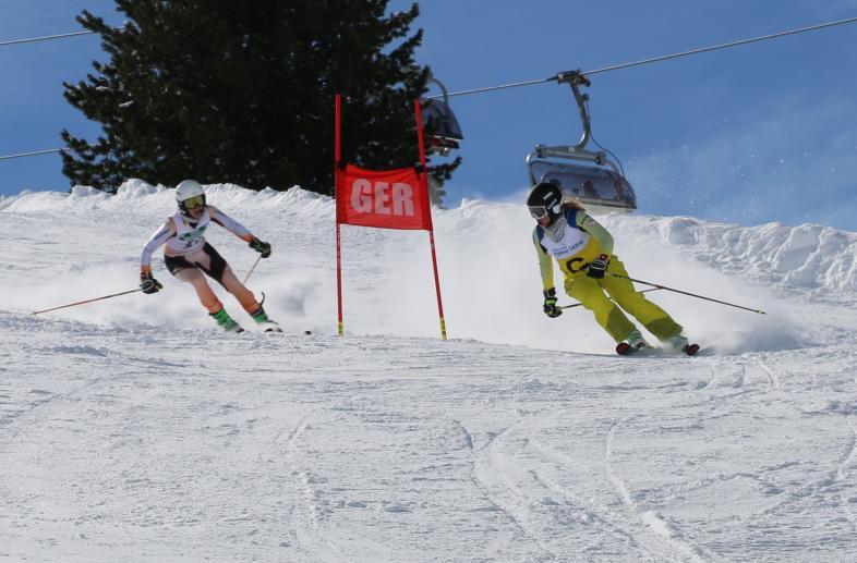 Noemi Ristau mir Guide auf der Piste: Der Himmel ist blau, die Schneeverhältnisse prima, beide umfahren ein Slalomtor.
