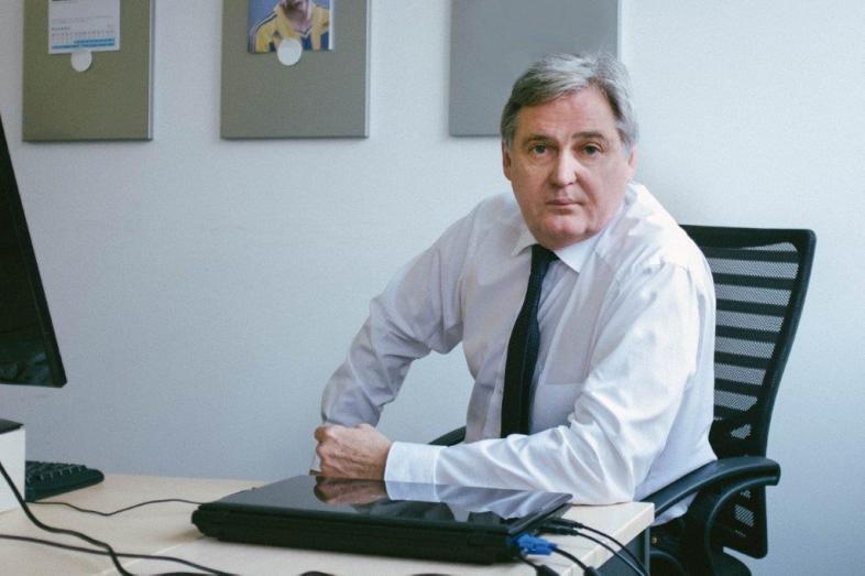 Rudi Ullrich sitzt am Schreibtisch, er trägt Hemd und Kravatte.