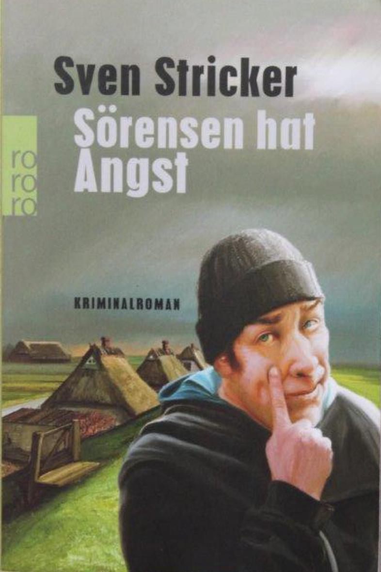 Das Buchcover zeigt einen Mann mit ängstlichem Gesichtsausdruck, im Hintergrund erkennt man Geestlandschaft und Reetgedeckte Häuser