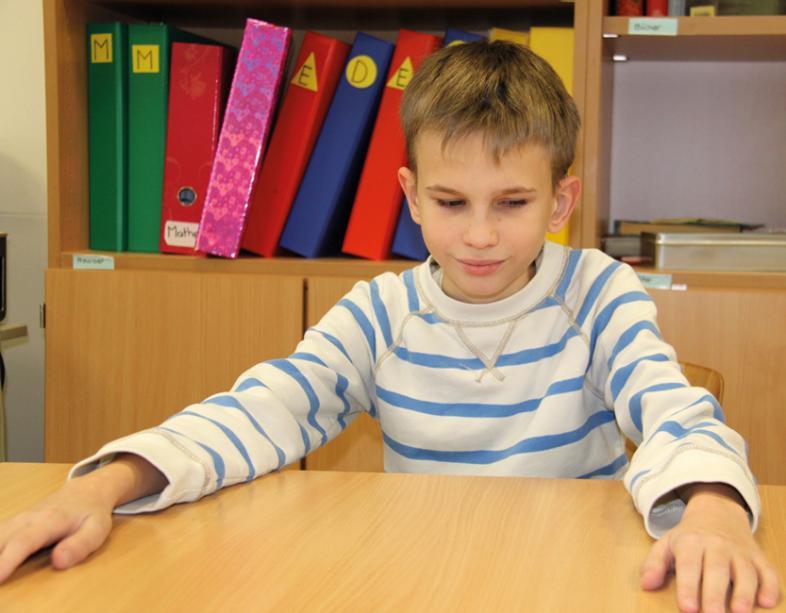 Das Foto zeigt einen Jungen, der - seine Arme breit aufgestützt - lächelnd am Schreibtisch sitzt.