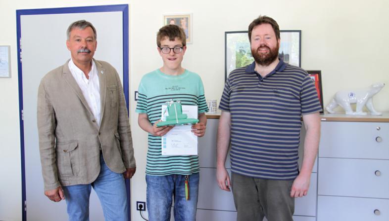 Das Foto zeigt Tom, er hält seine Auszeichnung in den Händen und steht zwischen den Herren Lembke und Feldmann
