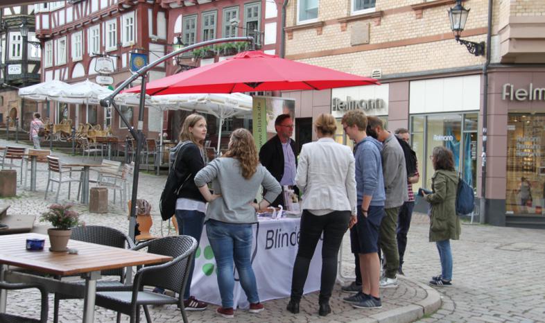 Um den Informationsstand mit rotem Schirm sind Personen im Gespräch miteinander