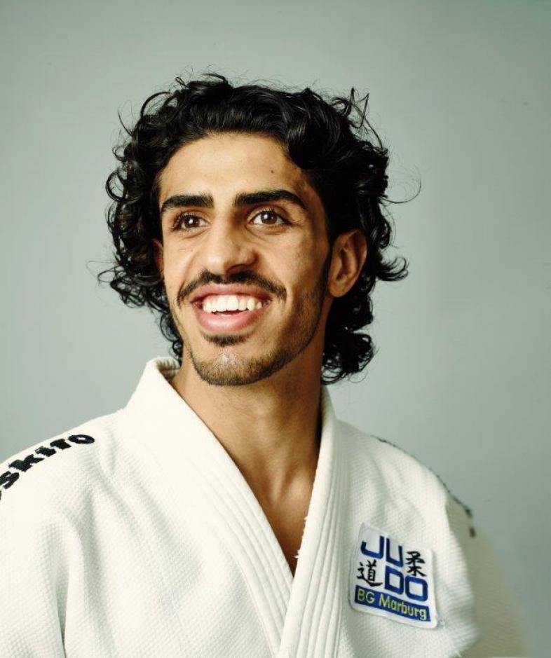 Portraitfoto im Judodress: Shugaa hat dunkle Locken und einen Kurzbart, er lacht vergnügt.