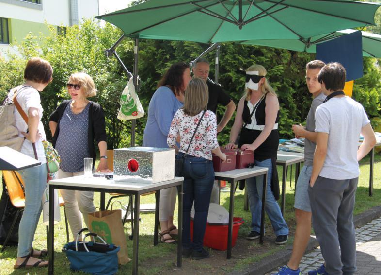 Rund um einen Stand mit grünem Sonnenschirm stehen Besucher
