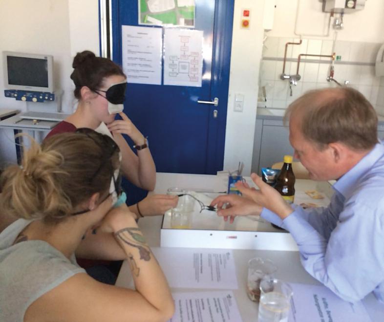Herr Mahnke erläutert zwei Studentinnen die Aufbereitung der Aufgaben für blinde und sehbehinderte Schülerinnen und Schüler