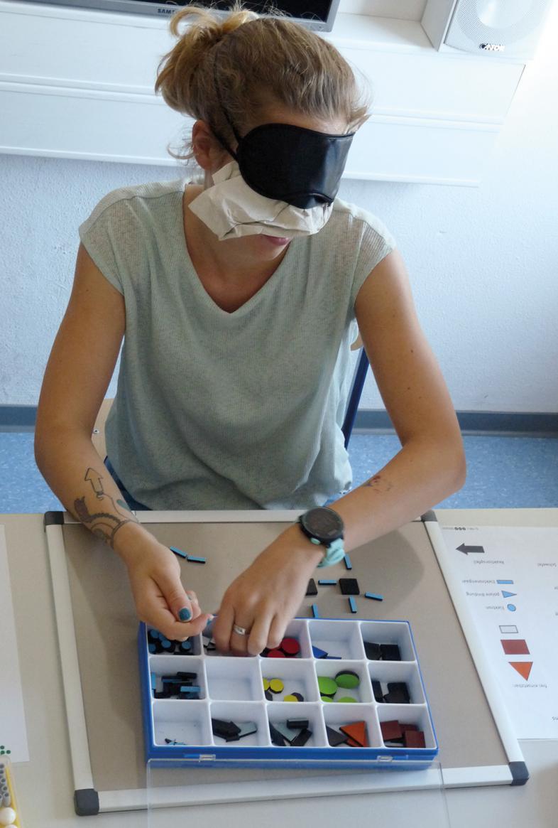 Eine junge Frau ertastet unter der Augenbinde die Elemente des Chemie-Baukastens