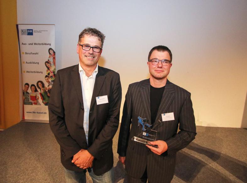 Otfrid Altfeld und Thilo Lutz schauen lächelnd in die Kamera, Thilo hält seine Auszeichnung in den Händen