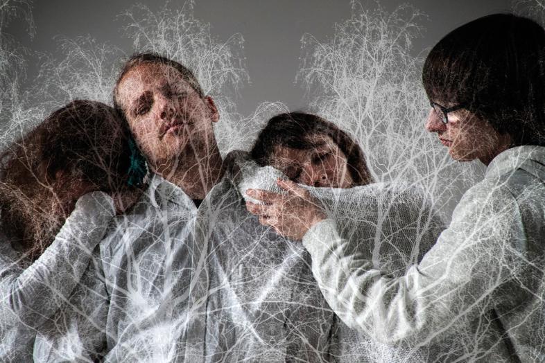 Eine Szene zeigt 4 Schauspieler hinter vernetzten Strukturen