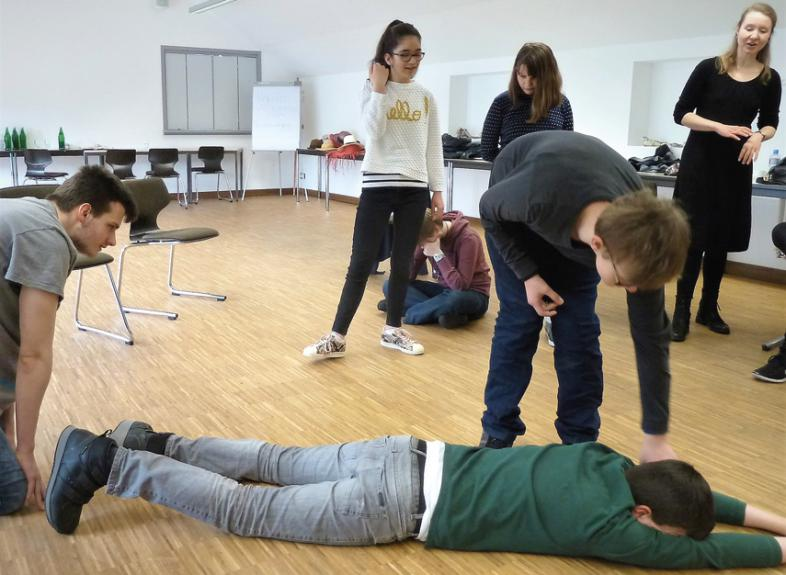 Theaterszene mit 6 Akteuren. Einer der jungen Leute liegt am Boden, ein anderer beugt sich zu ihm hin.