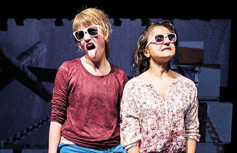 Eine Szene aus dem Theaterstück zeigt zwei Mädels mit Sonnenbrillen