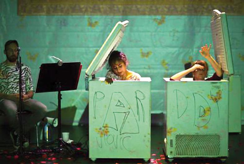 Eine Szene aus dem Theaterstück  zeigt 2 Personen, die in grünen Kisten sitzen