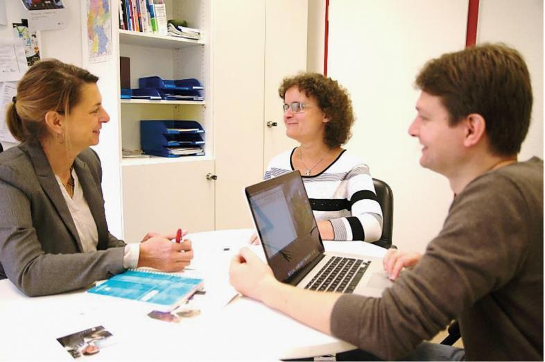 Beratungsgespräch: 3 Personen sitzen um einen Tisch