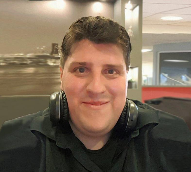 Portraitfoto von André Tolzmann, er trägt die Kopfhörer heruntergeschoben und lächelt
