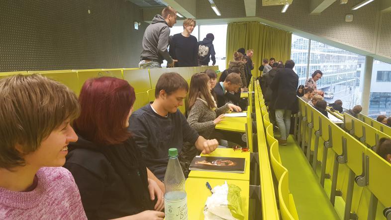 Die Schüler besichtigen einen Vorlesungsraum mit hoch klappbaren Sitzen und herunter ziehbaren Tischen