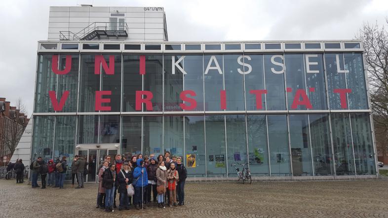 Die Abschlussklassen der drei Fachoberschulen stehen vor einem gläsernen Gebäude der Uni Kassel