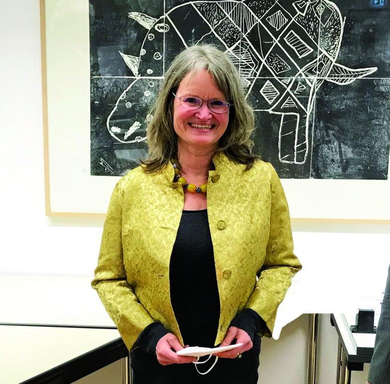 Halbportrait-Foto von Ulrike Schönhagen, sie trägt ein schwarzes Kleid und eine gelbe Jacke und lächelt