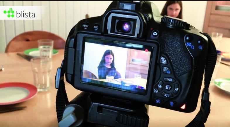Bild der Videokamera aus der Bedienersicht, so dass im Hintergrund das die echte Emilie zu sehen ist und auf dem Display die aufgenommene Emilie