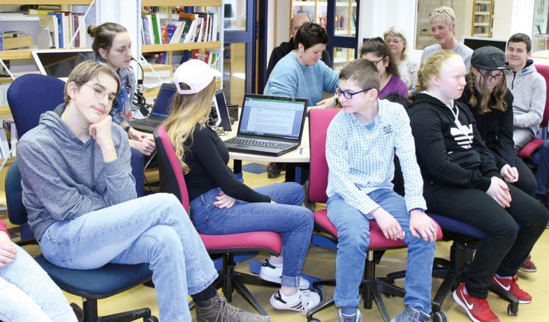 8 Schülerinnen und Schüler sitzen um einen Laptop