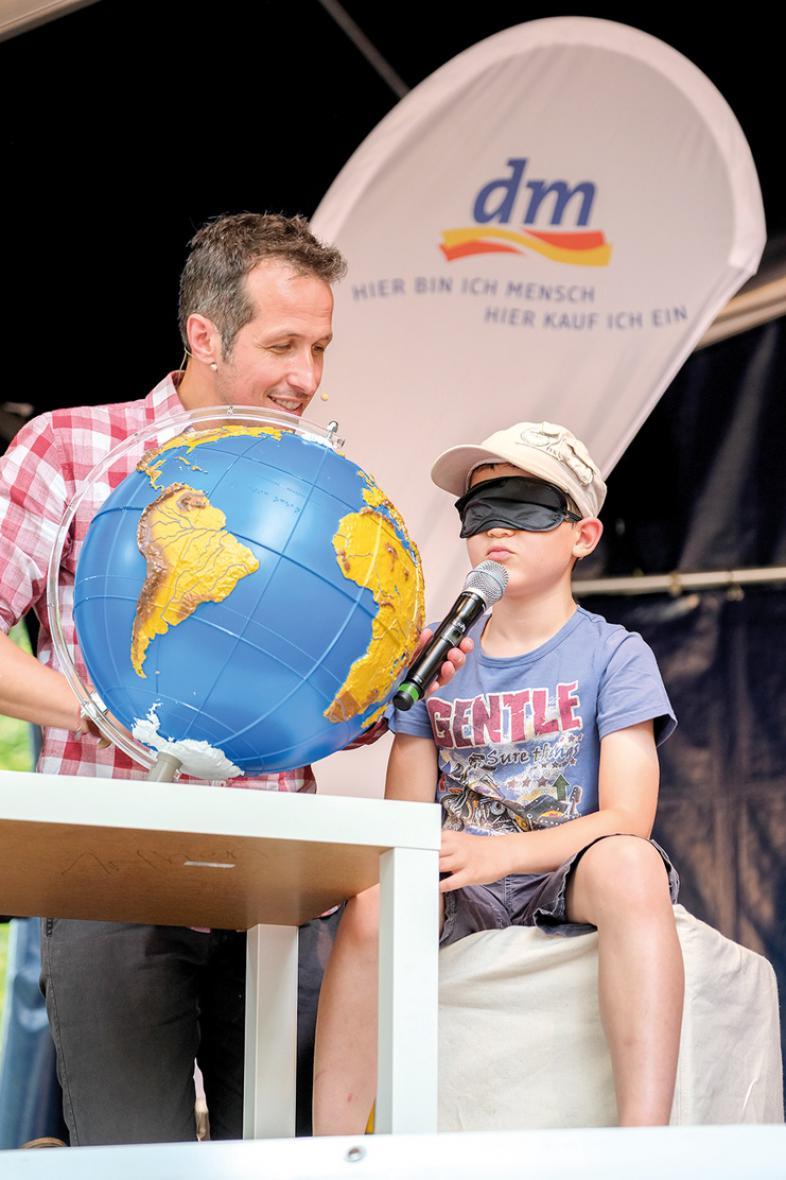 Willi Weitzel zeigt auf der Bühne einem Kind einen taktilen Globus