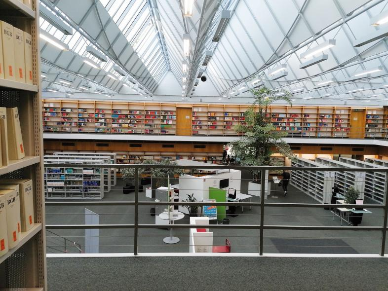 Foto vom Blick in die Uni-Bibliothek in Tübingen von einer offenen Galerie aus. Es sind viele Bücherregale mit sehr großen Lücken zu sehen.