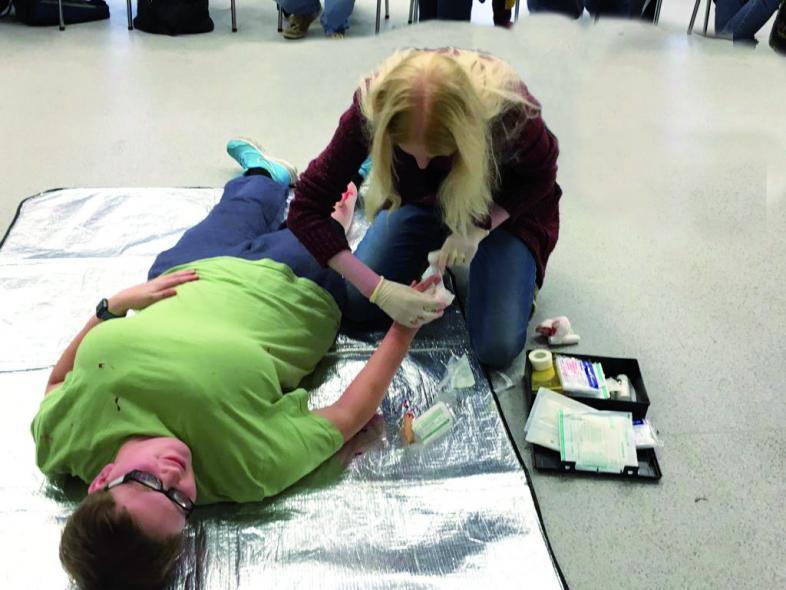 Szene aus einem Erste-Hilfe-Kurs: Die Hand einer liegenden Person wird verarztet