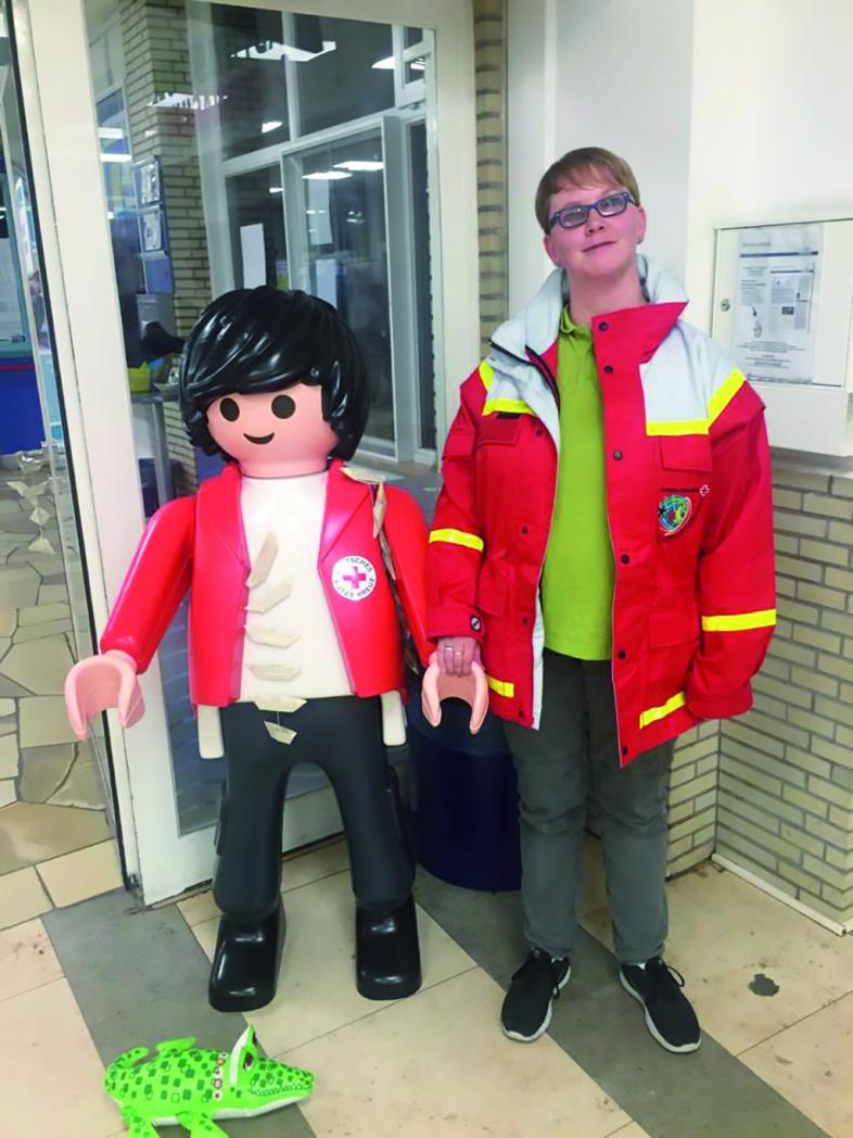 Lena Hörster mit Sanitäterjacke neben einem kindergroßen Playmobil-Sanitäter