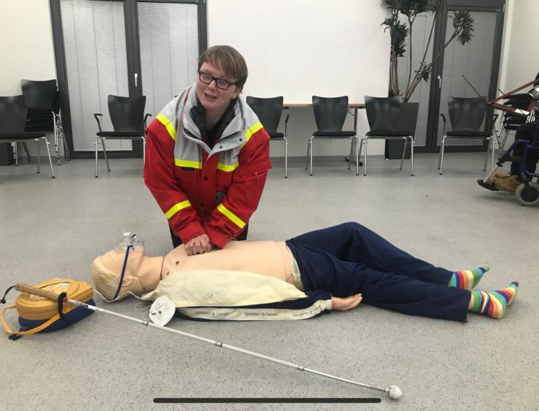 Lena Hörster zeigt an einem Dummy die Herzdruckmassage
