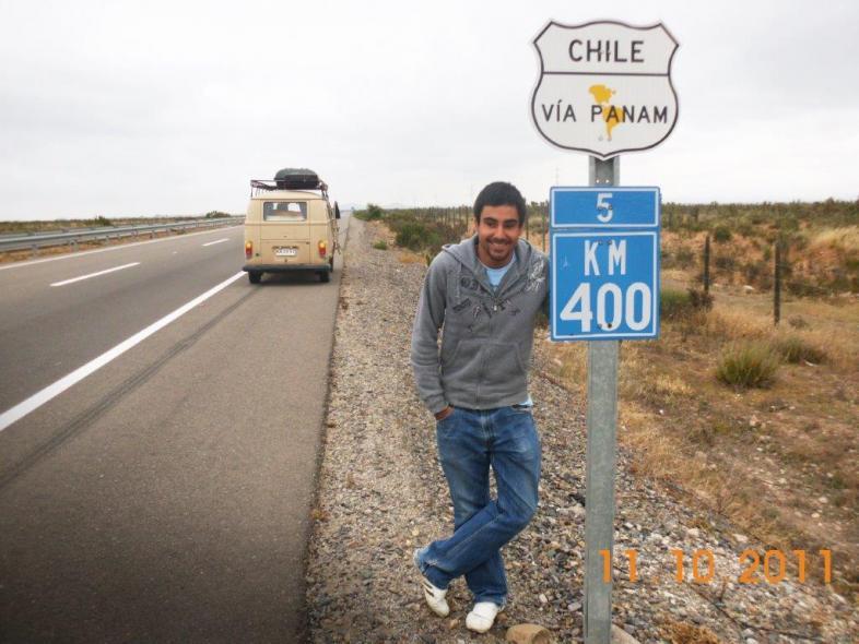 """Der junge Mann steht lachend an einem Straßenschild """"chile via Panam 400 km"""""""