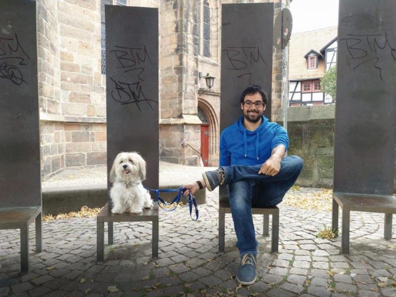 Der Junge Mann sitzt lachend auf dem Platz vor der Alten Universität in Marburg, er hält einen Hund an der Leine.