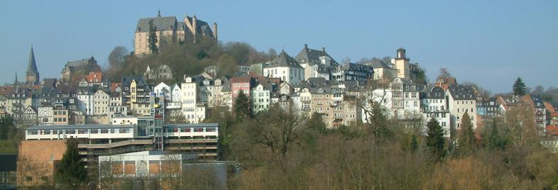 Das Foto zeigt die Marburger Oberstadt mit dem Schloss vor stahlblauem Himmel