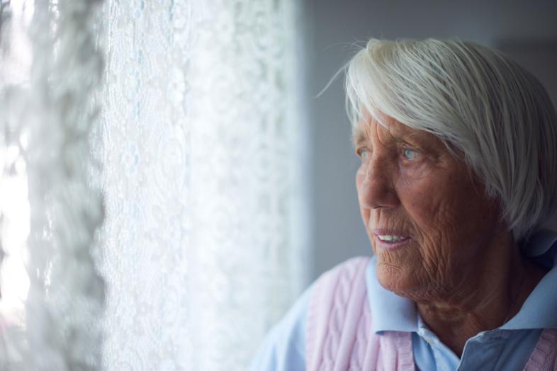 Eine ältere Dame steht am Fenster