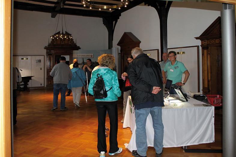 Besucher informieren sich an den Thementischen vor dem Rathaussaal