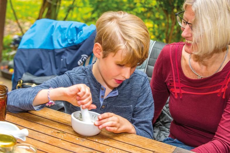 Ein Junge zerkleinert Apfelschnitze in einem Mörser