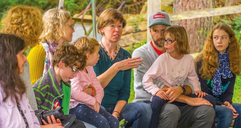 Eltern und Kinder sitzen vergnügt auf einer Bank
