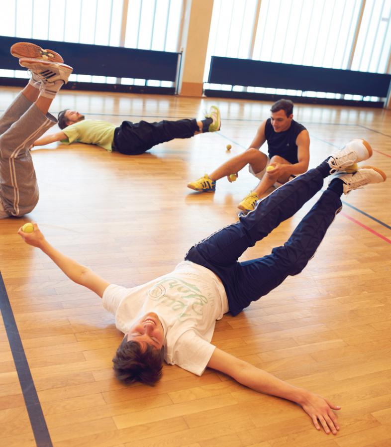 4 Teilnehmende machein eine Übung im Liegen und balancieren dabei einen Tennisball zwischen den Füßen.