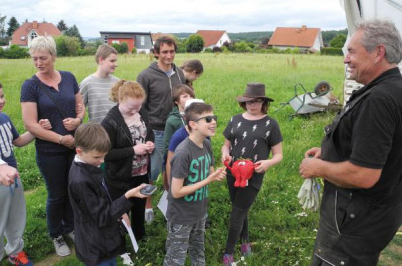 Die Klasse hört interessiert dem Gemüseanbauexperten zu