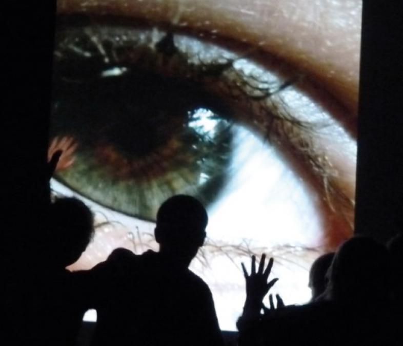 Das Bild einens Geöffneten Auges als Hintergrundszenerie der Aufführung