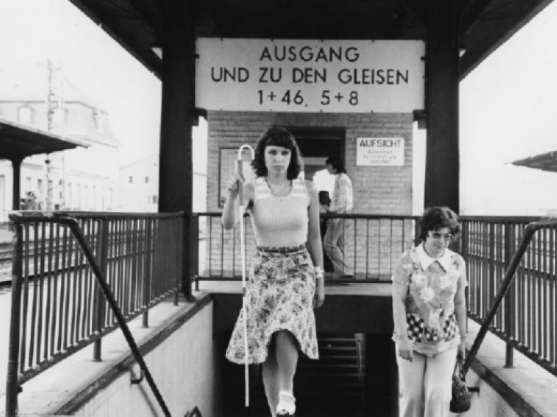 Orientierung und Mobilität in den 1970ern. Eine junge Frau geht die Stufen zum Gleis am Marburger Bahnhof hoch.