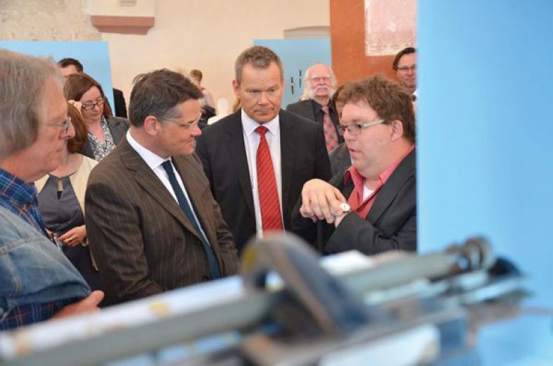 Thorsten Büchner führt Minister Boris Rhein und Marburgs Oberbürgermeister Thomas Spies durch die Ausstellung