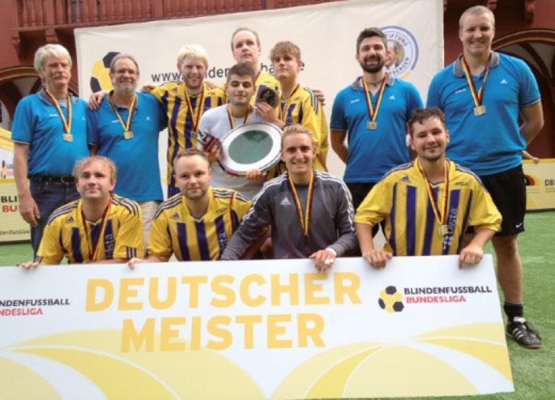 """Das Meisterteam und seine Betreuer mit umgehängten Medaillen hinter einem Plakat mit der Aufschrift """"Deutscher Meister"""""""