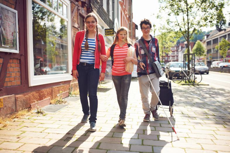 Drei blista-Schülerinnen und Schüler laufen mit einem Langstock auf einem Gehweg