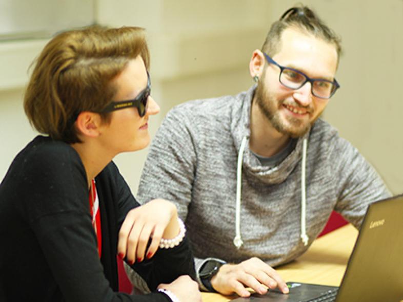 2 Azubis im Gespräch vor dem Laptop