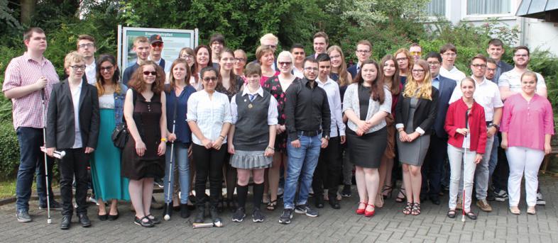 Das Gruppenfoto zeigt die Absolventinnen und Absolventen vor der Sporthalle
