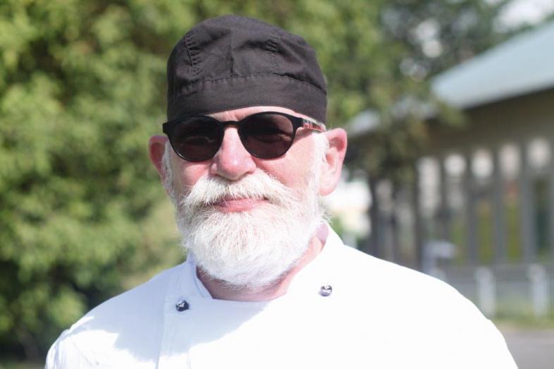 Portraitfoto Peter Wiersbin, lächelnd trägt der bärtige Mann mit Sonnenbrille eine schwarze Kochmütze, eine weiße Jacke