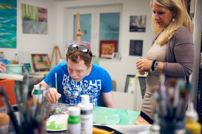 Ein junger Mann sitzt an einem Tisch mit Malutensilien und malt, während eine Frau neben ihm steht und interessiert auf das Bild schaut.